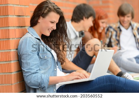 Student girl working on laptop outside college friends in background - stock photo