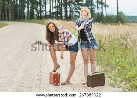 Student girls are funny grimacing and hitchhiking on dirt summer road at farm fiel and forest background - stock photo
