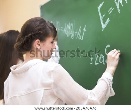 Student girls writing on the blackboard in the classroom - stock photo