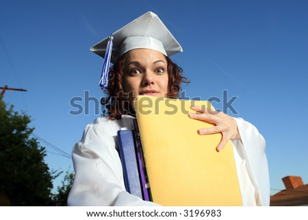 Student holding a big pile of textbooks and folders - stock photo