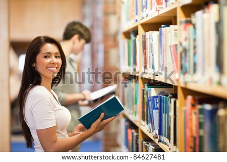 Student holding a book while looking at the camera - stock photo