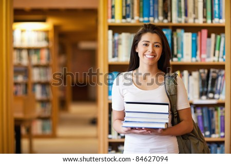 Student holding books in the library