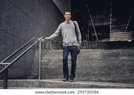 Student in blue jeans and grey jacket going down on steps. - stock photo
