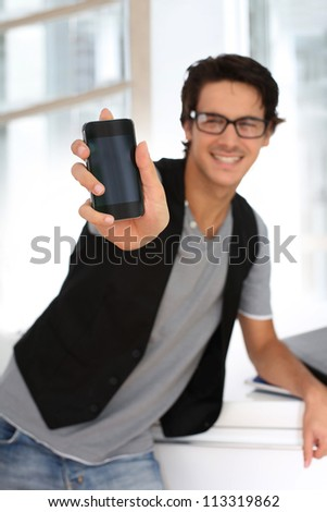 Student in building showing smartphone to camera - stock photo