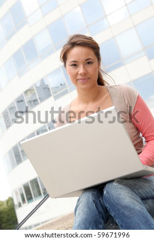 Student in college campus with laptop computer - stock photo