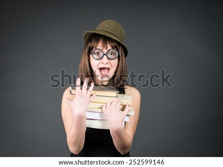 Student in funny glasses with books on grey. Nerd girl studying. Education. - stock photo