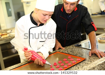 Student in pastry making cookies with help of teacher - stock photo
