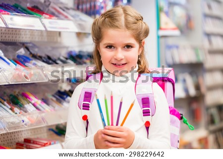 Student in stationery store buying pens holding them into the camera - stock photo