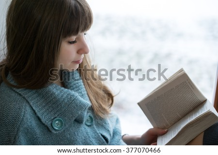 Student in warm clothes reading a book on window frame during winter.