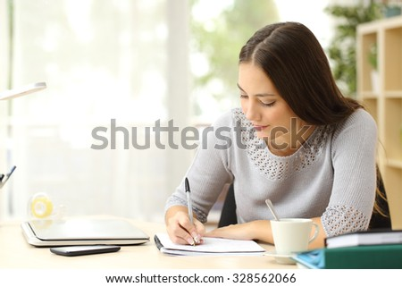 Student learning and taking notes on a desk at home - stock photo