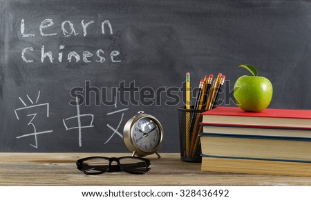 Student learning Chinese with books, pencils, clock, reading glasses and an apple in front of chalkboard with Mandarin text.  - stock photo
