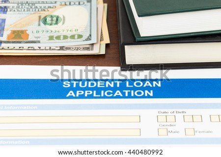 Student loan application form with dollar banknote, and text book