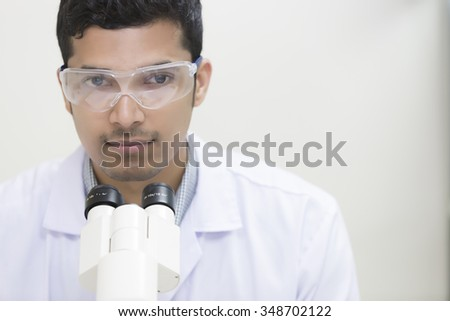 student male looking in a microscope, science laboratory concept