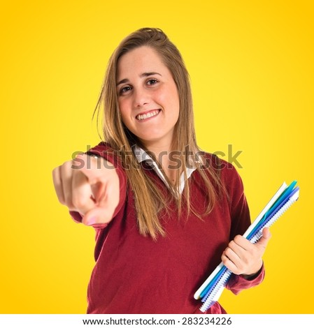 Student pointing to the front over colorful background - stock photo