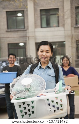 Student portrait in front of dormitory at college with family - stock photo