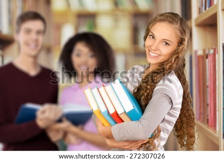 Student. Pretty Female Student Surrounded by Library Books - stock photo