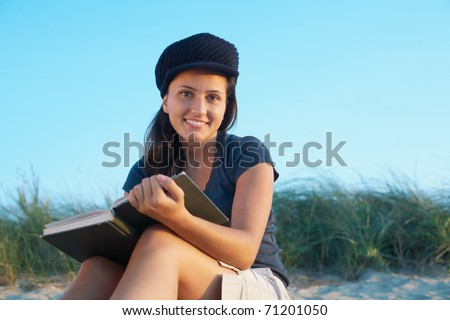 Student pretty young woman with book on the beach - stock photo