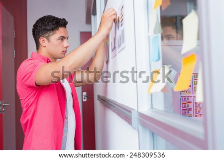 Student putting graphics on the wall at the college