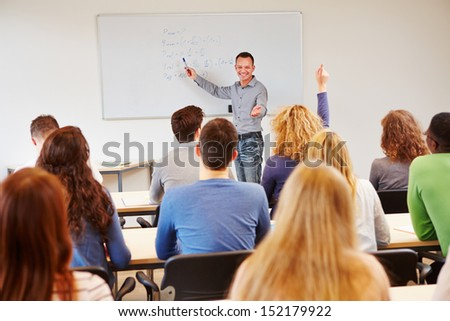 Student raising hand in school class and getting called by teacher - stock photo
