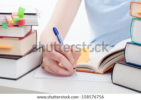 Student reading a book and writing the notes - stock photo