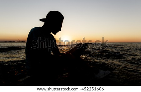 Student reading a book by the sea at sunset