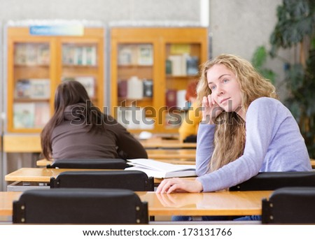 student reading a book in the library - stock photo