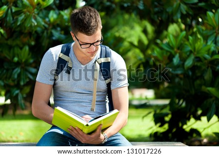 Student reading a book in the park - stock photo