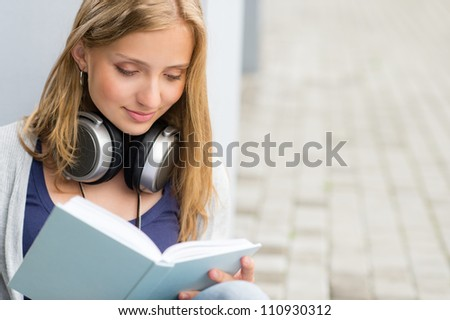 Student reading a book outside of university woman happy study