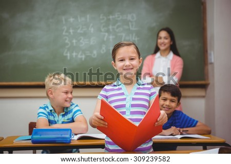 Student reading from a book at the elementary school - stock photo