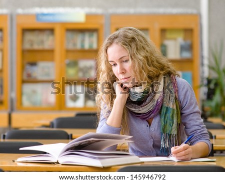 student reads the book in library  - stock photo