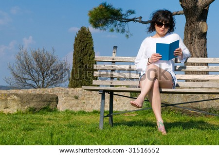 Student reads the book sitting on a bench in the garden university - stock photo