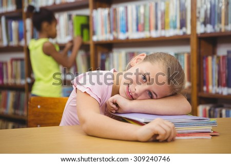 Student resting her head on some books at the elementary school library - stock photo