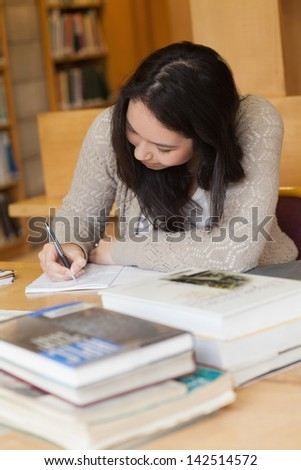 Student sitting at a desk in a library while writing in a notepad and learning - stock photo