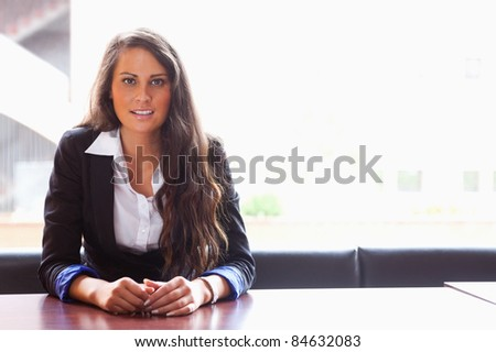 Student sitting at a table while looking at the camera - stock photo