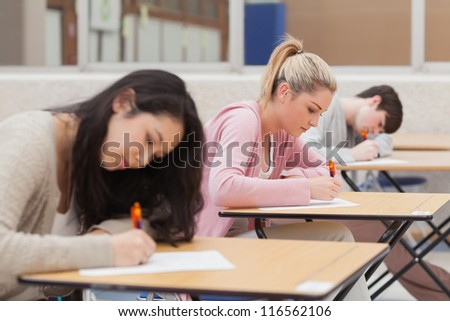 Student sitting at desks writing during an exam in college