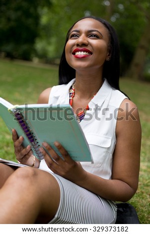 student sitting in the park holding her textbook