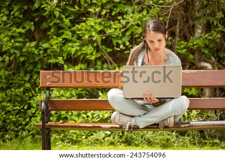 Student sitting on bench listening to music and using laptop and wearing headphones - stock photo