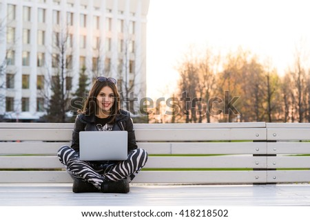 Student sitting on bench listening to music and using laptop smiling against university campus - stock photo
