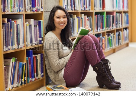 Student sitting on the floor in a library and leaning against a shelf while holding a book