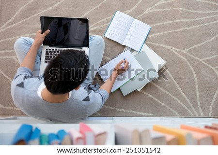Student sitting on the floor with a laptop and doing homework, view from above - stock photo