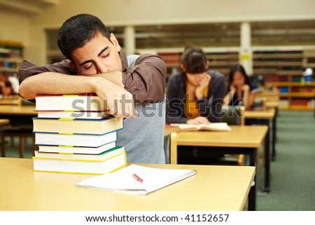 Student sleeping in reading room of university library - stock photo