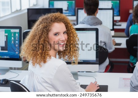 Student smiling at camera in computer class at the college