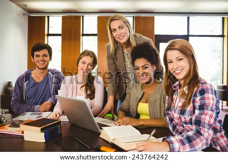 Student smiling at the camera with their teacher in library - stock photo