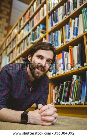 Student smiling on floor in library wearing smart watch at the university