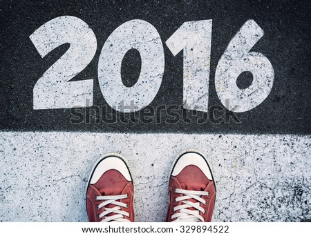 Student standing above the sign for New Year 2016 - stock photo