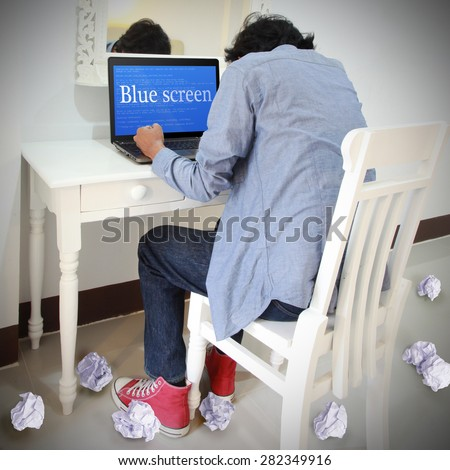 Student stressed computer user Business laptop or office notebook computer PC with OS critical error message on blue screen display. He will  loss data with out save file. - stock photo