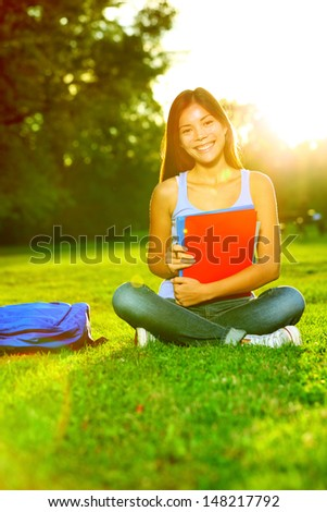 Student studying in park going back to school at university college. Happy asian girl student sitting studying, writing and reading outside. Multi ethnic Chinese Asian / Caucasian female student woman - stock photo