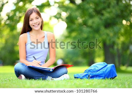 Student studying in park. Joyful happy asian girl student sitting writing and reading outside on university campus or park. Mixed race Chinese Asian / Caucasian female student woman looking at camera. - stock photo