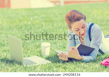 Student studying in park. Joyful happy young girl student sitting reading book outside on university campus or park. Education concept. Positive face expression  - stock photo