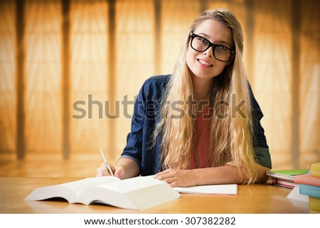 Student studying in the library against window overlooking city - stock photo